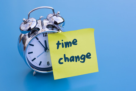 alarm clock on blue table with sticky note time change Stock Photo
