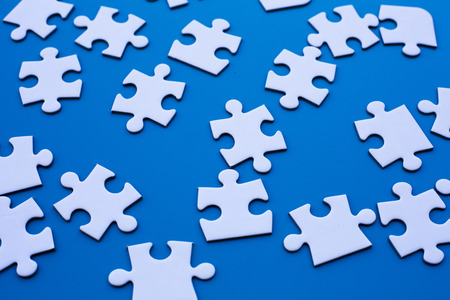 jig: white puzzle on blue table Stock Photo