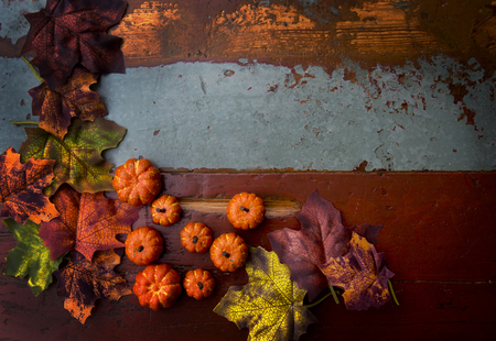 Old vintage table with pumpkins and leaves