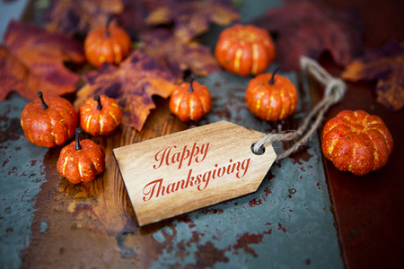 thanksgiving: Happy Thanksgiving on wooden tag with pumpkins and leaves