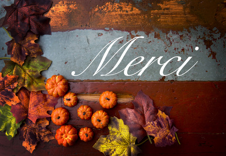 french word 'merci' thank you on old vintage wood with pumpkins and leaves Stock Photo
