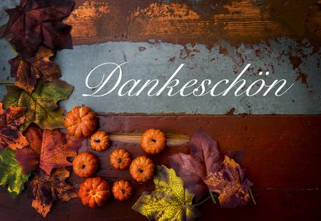 Duitse woord 'Thank You' dank u op oude vintage hout met pompoenen en bladeren