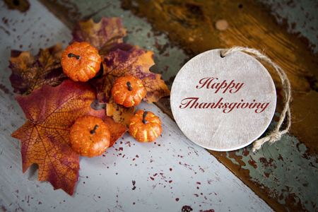 Happy Thanksgiving on wooden tag with pumpkins and leaves