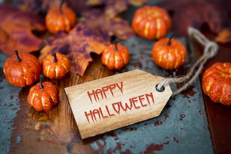 Happy Halloween op houten tag met pompoenen en bladeren