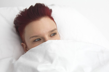 wellness sleepy: red-haired woman lying in bed in white bedsheets Stock Photo