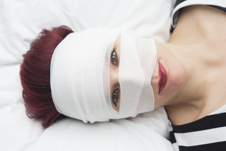 aging woman: closeup of beautiful woman in bed with bandages wrapped around her head