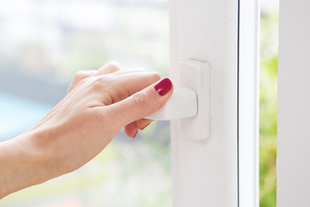 closeup of womans hand opening a window