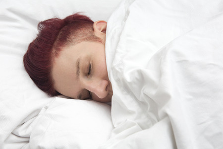 wellness sleepy: red-haired woman sleeping in bed on white bedsheets