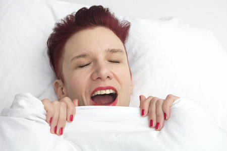 wellness sleepy: red-haired woman lying in bed and is yawning