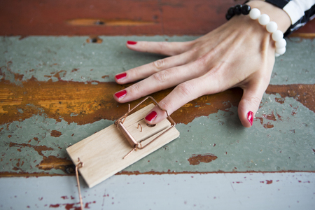 nailpolish: closeup of womans finger with red nailpolish in mousetrap