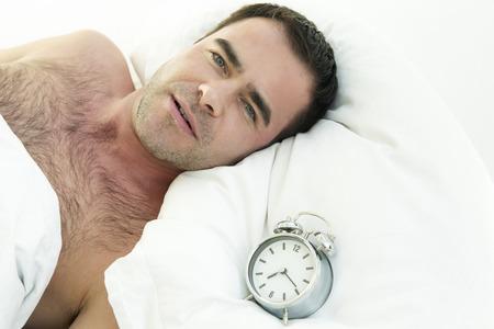 wellness sleepy: shirtless man in bed with alarm clock