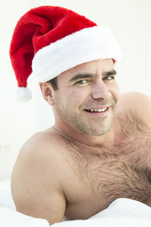 bed time: man with santa hat lying in bed and looking at camera