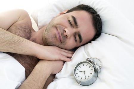 wellness sleepy: shirtless man sleeping with alarm clock on pillow