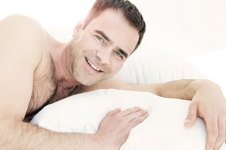 wellness sleepy: shirtless man in bed and smiling at camera Stock Photo