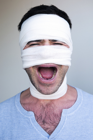 screaming head: portrait of screaming man with bandages wrapped around his head