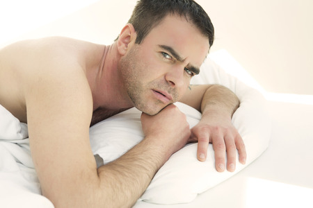 wellness sleepy: shirtless man lying in bed and looking at camera Stock Photo