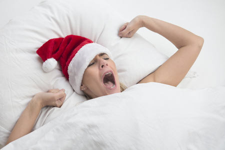 wellness sleepy: woman lying in bed and yawning and wearing a Santa hat