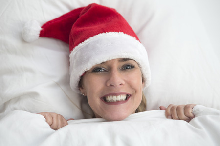 wellness sleepy: woman in bed with Santa hat looking at camera Stock Photo