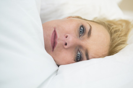 wellness sleepy: blond woman lying in bed and looking at camera