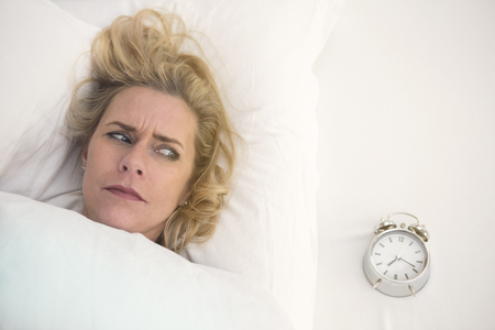 wellness sleepy: blond woman in bed looking annoyed at her alarm clock