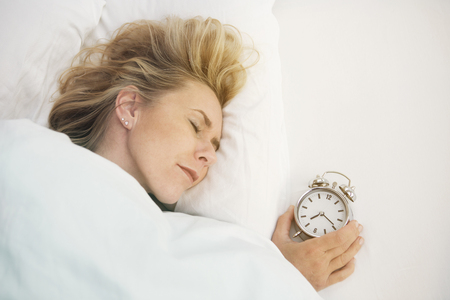 wellness sleepy: blond woman sleeping in bed with alarm clock next to her