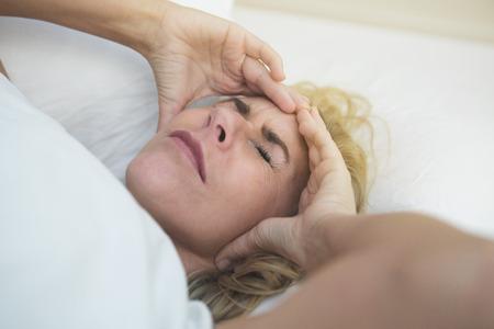 personne malade: femme blonde dans le lit avec des maux de t�te