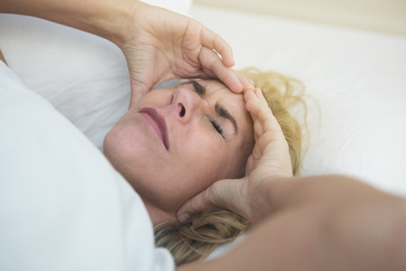 persona enferma: mujer rubia en la cama con dolor de cabeza