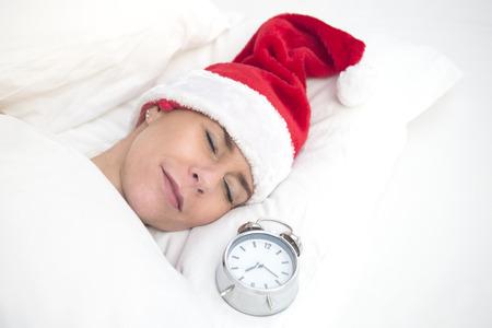 christmas morning: woman in Santa hat sleeping next to alarm clock