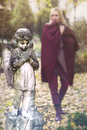grief: woman walking in cemetery next to statue of little angel