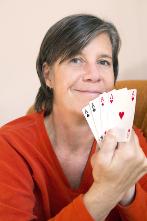 aces: woman playing cards and holding four aces