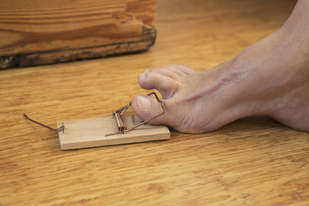 caught: foot caught in mousetrap on wooden floor Stock Photo