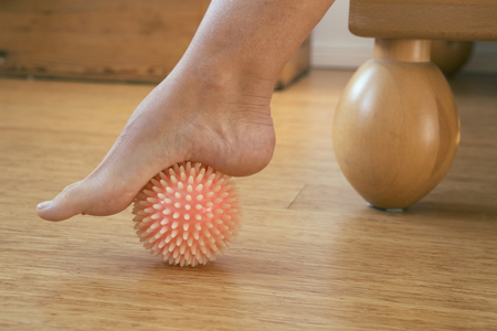 woman foot: foot in with rubber massage ball