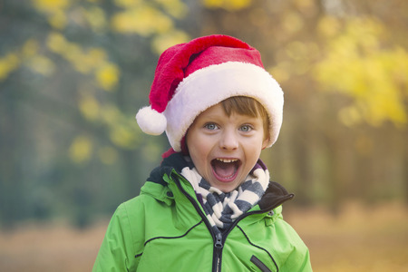 jungle boy: portrait of a boy with Santa hat in park in the fall Stock Photo