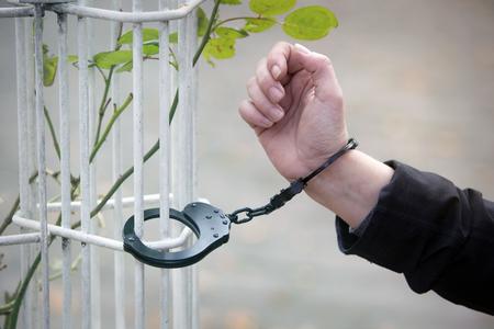 rejas de hierro: primer plano de la mano est� esposado a barras de hierro