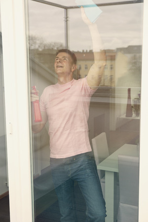 houseman: handsome man cleaning a big window Stock Photo