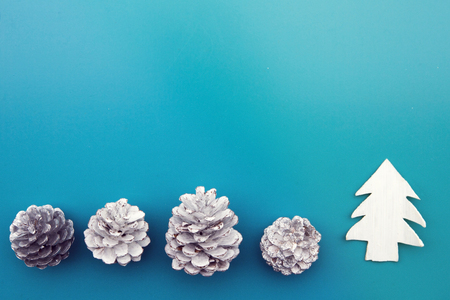 pinecones: white pinecones and toy tree on blue background