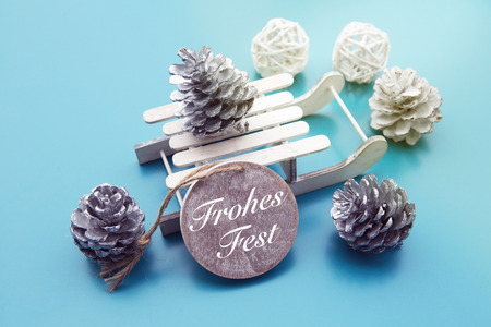 pinecones: German Merry Christmas Merry Christmas on wooden tag with toy sleigh and pinecones