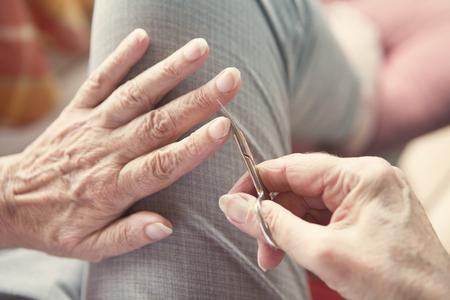 closeup of woman's hand cutting her fingernails