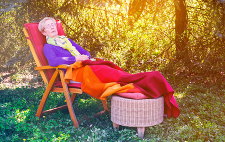 asleep chair: senior woman lying in chair in the garden and is sleeping Stock Photo