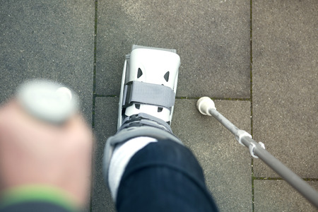 plaster cast: closeup of person walking with a plaster cast and crutches Stock Photo