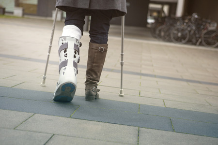 recovering: closeup of woman walking with a plaster cast and crutches