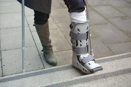 石膏のギプスと松葉杖で歩いている女性のクローズ アップ