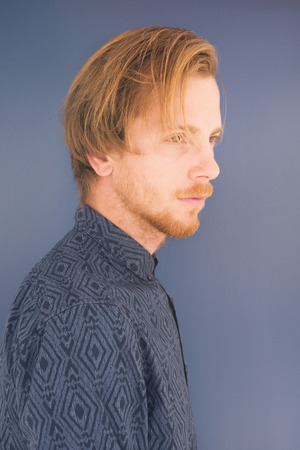 ginger hair: portrait of red-haired young man with blue background Stock Photo