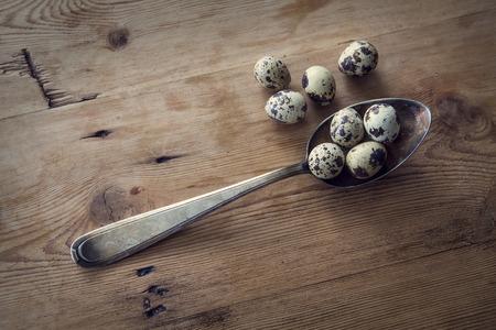 huevos de codorniz: cuchara de plata vieja con huevos de codorniz en mesa de madera