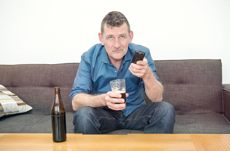 couch: man sitting on couch, drinking beer and watching tv