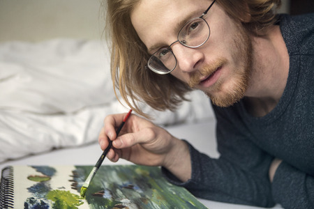 redhaired: red-haired young man lying in bed and painting a picture