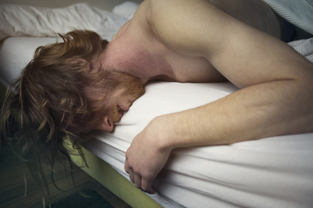 nude adult: red-haired young man lying in bed with nude upper body looking sick Stock Photo