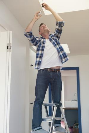 Man die op de ladder het verwisselen van een gloeilamp Stockfoto - 55861768