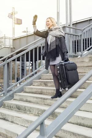 bajando escaleras: mujer rubia con la maleta en la estación de tren para bajar escaleras y saludar a alguien Foto de archivo