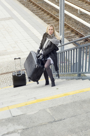 dragging: blond woman walking up stairs with heavy suitcases at train station Stock Photo